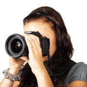 cámara digital niña mirando por objetivo sobre fondo blanco